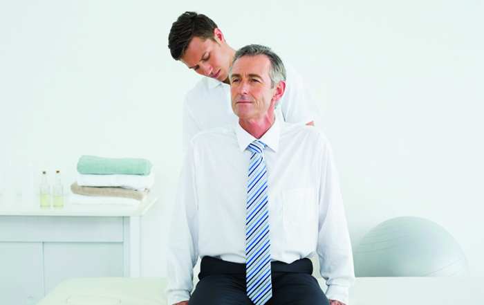 Male chiropractor examining mature man at office
